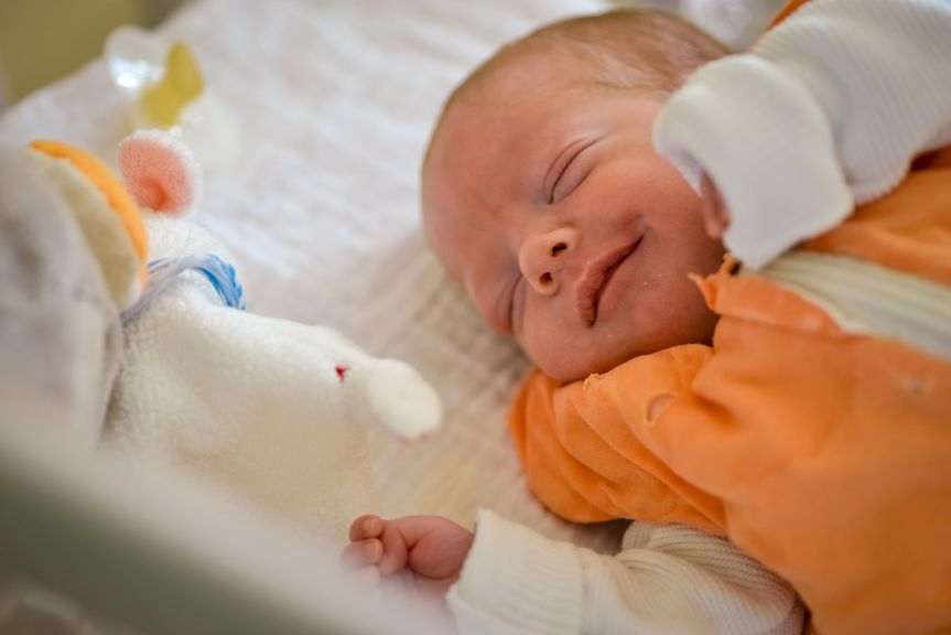Schlafendes Baby im Schlafsack, lächelnd