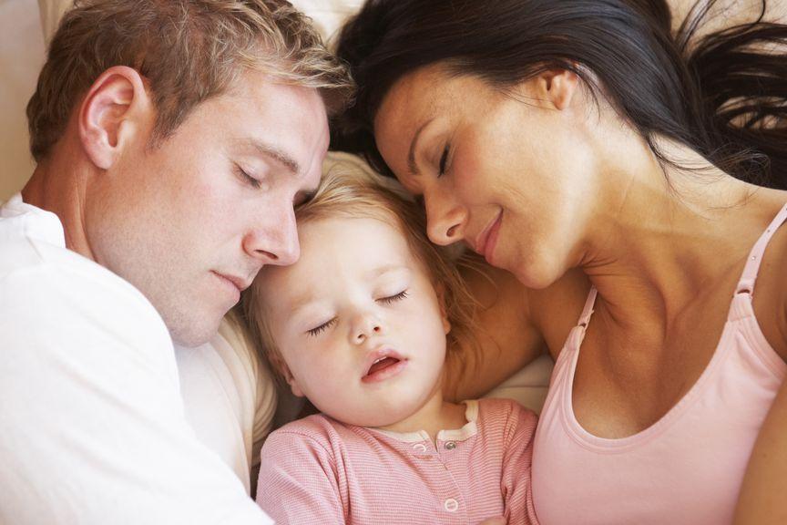 Eltern und Baby schlafen gemeinsam im Bett