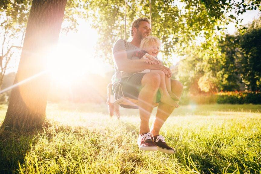 Vater und Sohn draussen auf der Schaukel in der Sonne