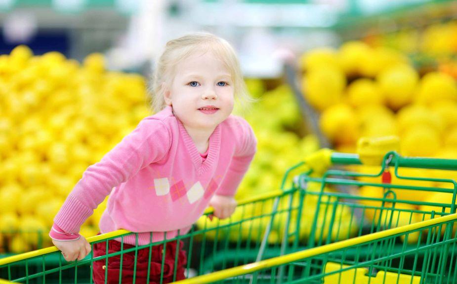 Kind klettert in Einaufswagen