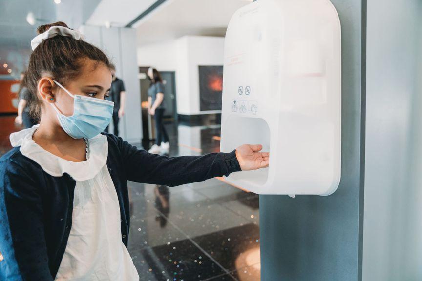 Mädchen am Desinfektionsmittelspender
