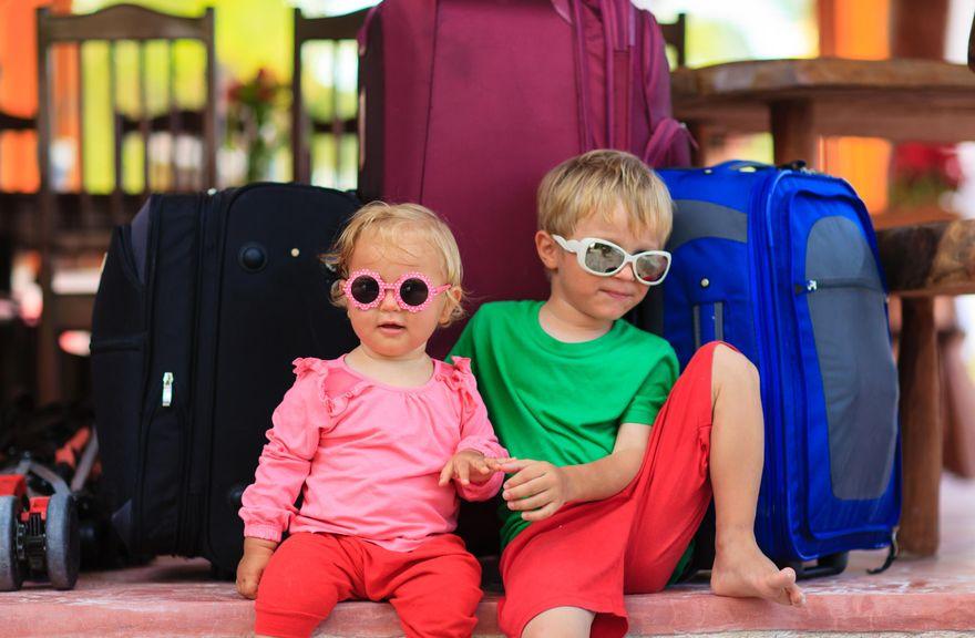 Geschwister sitzen vor gepackten Koffern