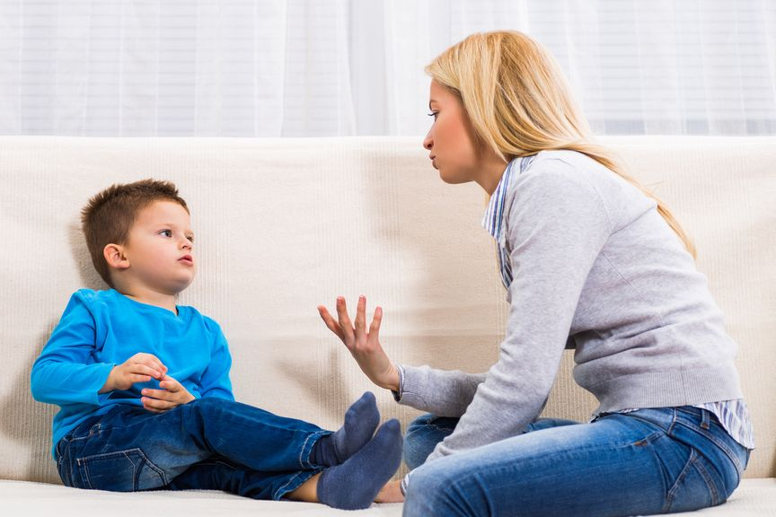 Mutter und Sohn sitzen auf dem Sofa und reden miteinander