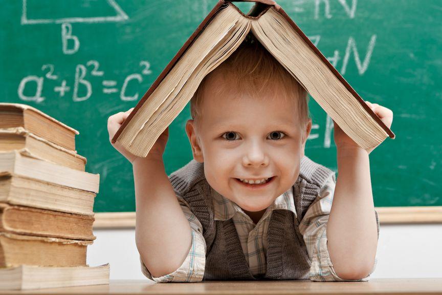 Kind sitzt vor der Tafel mit aufgeschlagenem Buch auf dem Kopf