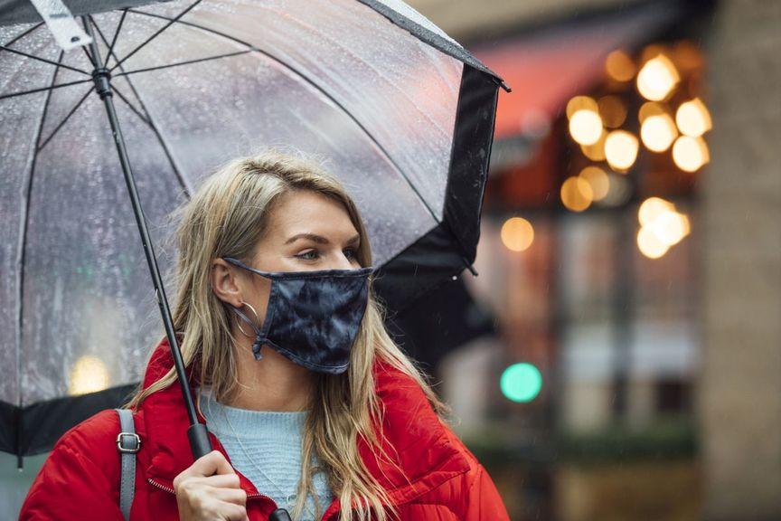 Frau mit Maske und Regenschirm