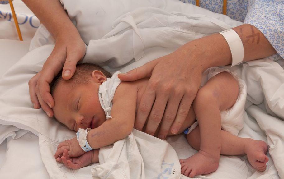 Hände der Mutter am Kopf und nacktem Bauch des Neugeborenen