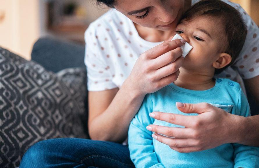 Erwachsene putzt Kind die Nase
