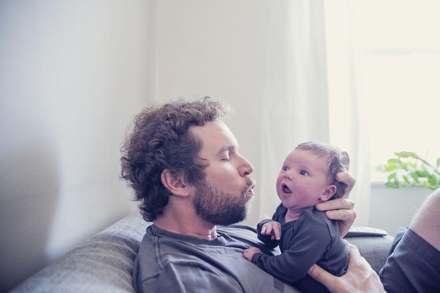 Vater sitzt mit Baby auf dem Sofa
