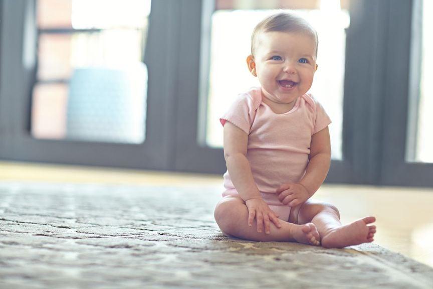 Strahlendes Baby sitzt auf dem Boden