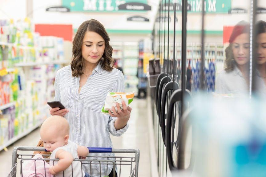 Mutter mit Baby im Supermarkt liest die Zutatenliste auf einer Lebensmittelpackung