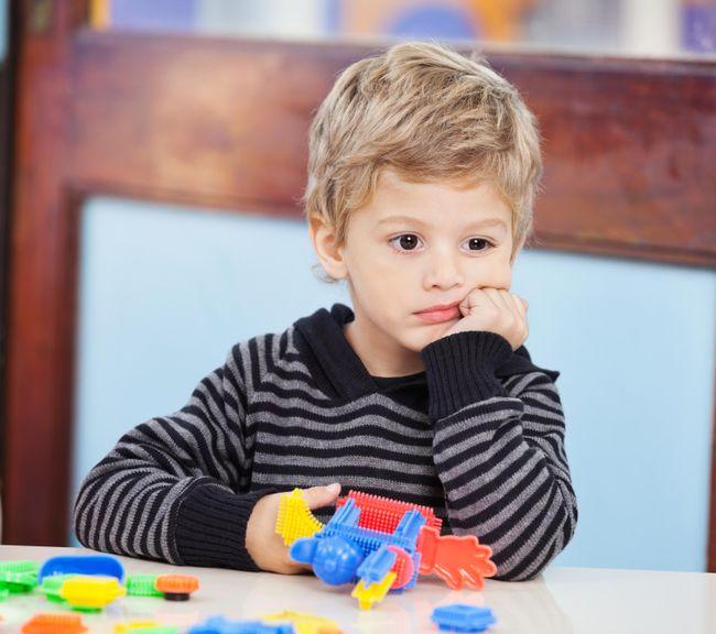 Kind sitzt am Tisch, Kinn auf Hand aufgestützt