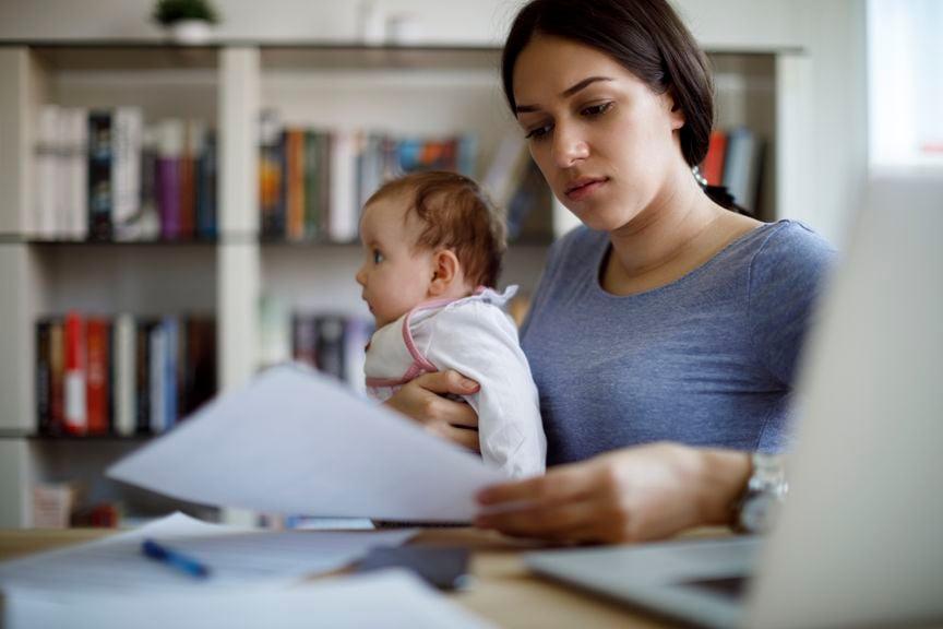 Mutter mit Baby liest Formulare