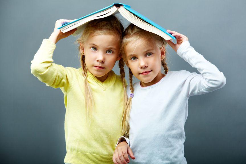 Zwillinge gemeinsam unter einem Buch