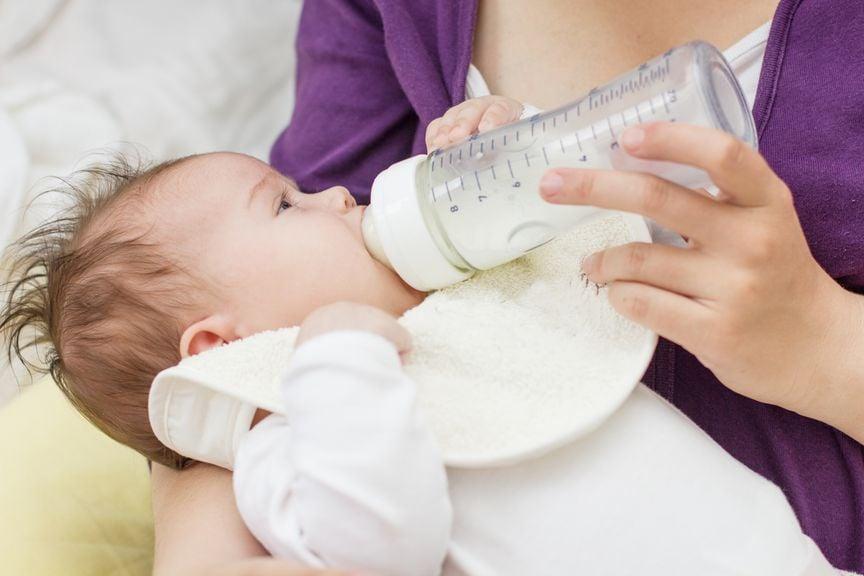 Baby im Arm der Mutter, wird mit dem Schoppen gefüttert