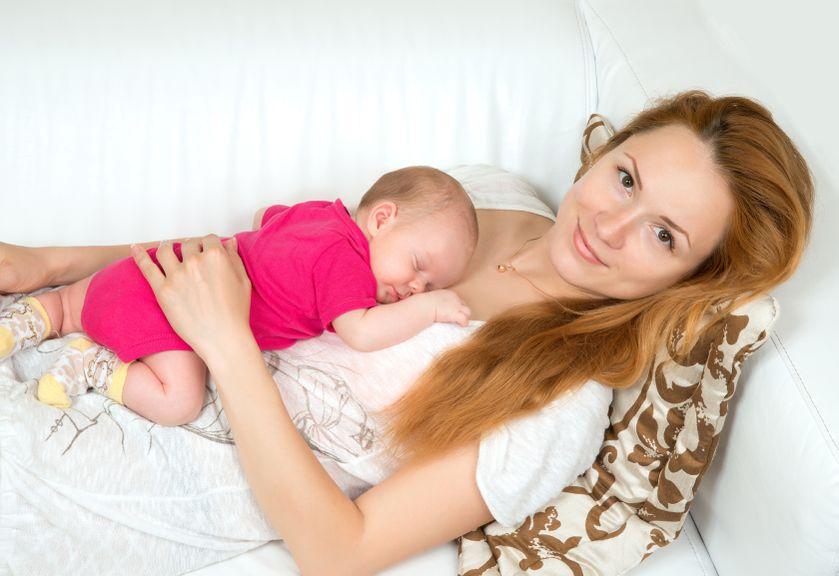 Mutter liegt auf dem Sofa mit Baby auf dem Bauch