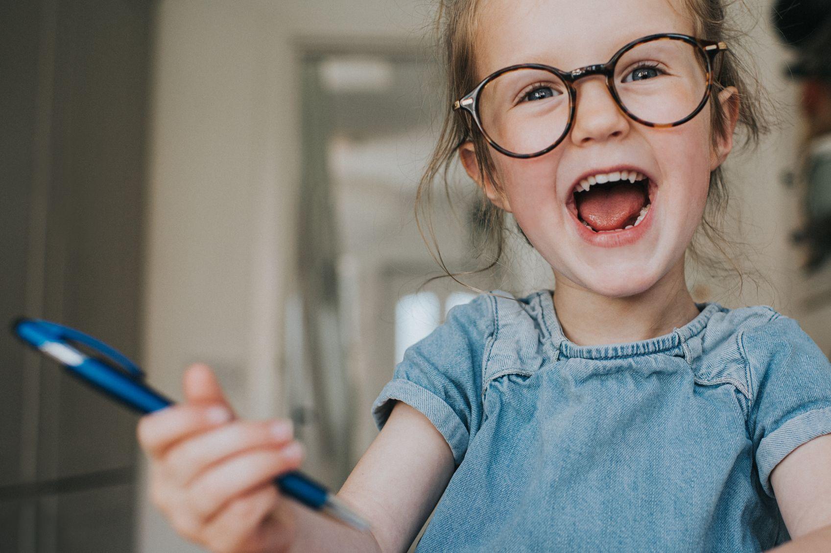Lachendes Mädchen mit Kugelschreiber in der Hand