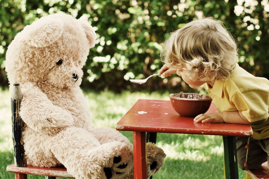 Kind füttert seinen Teddy