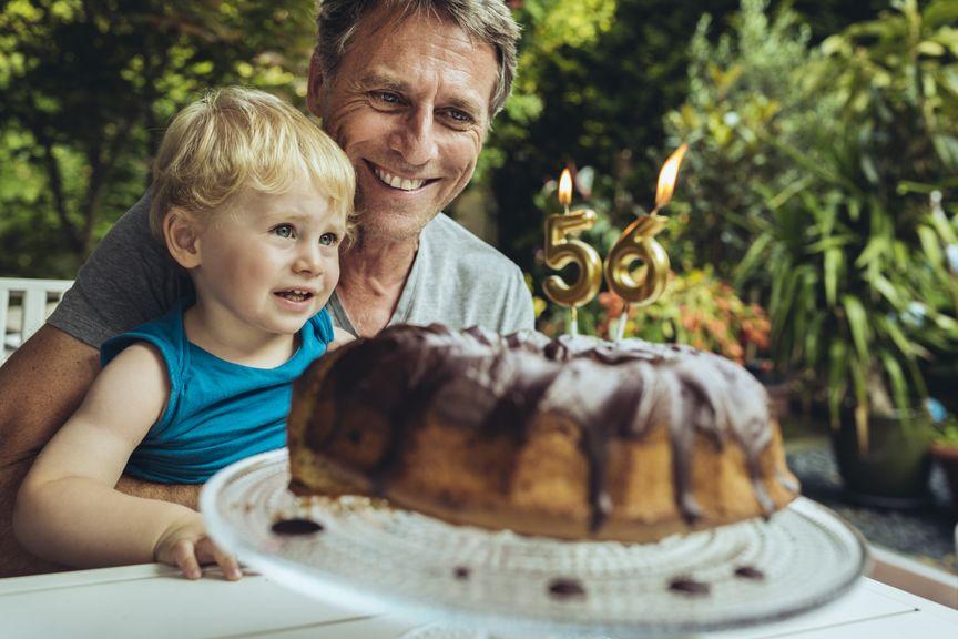 Kind mit Vater und einem Geburtstagskuchen