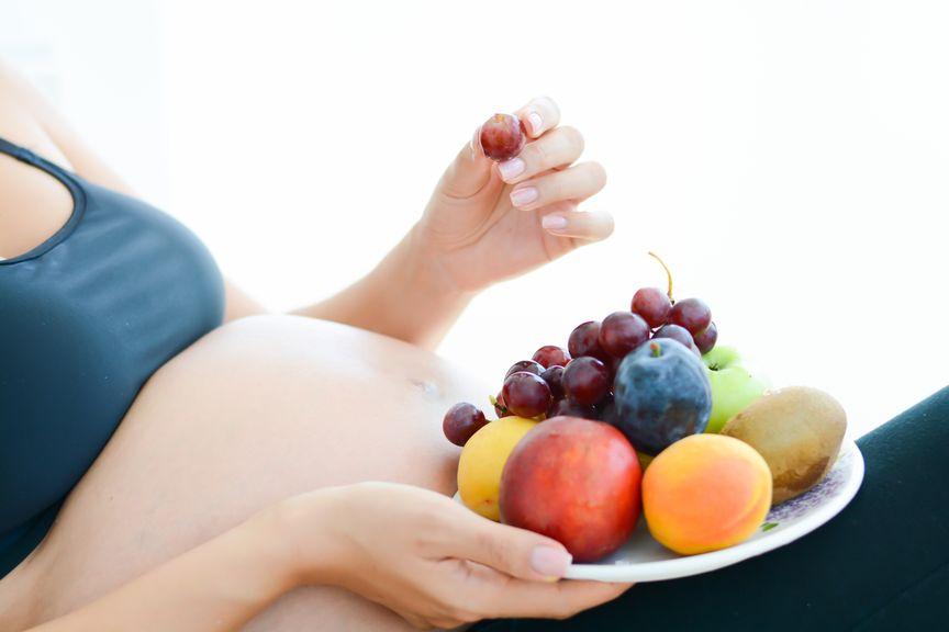 Schwangere mit einem Teller voll Früchten