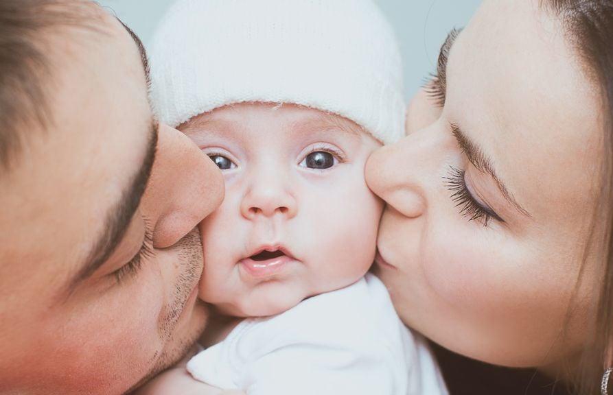 Paar küsst ihr Baby auf die Backe