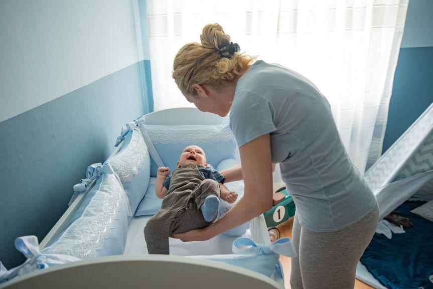 Mutter bringt ihr Baby ins Bett
