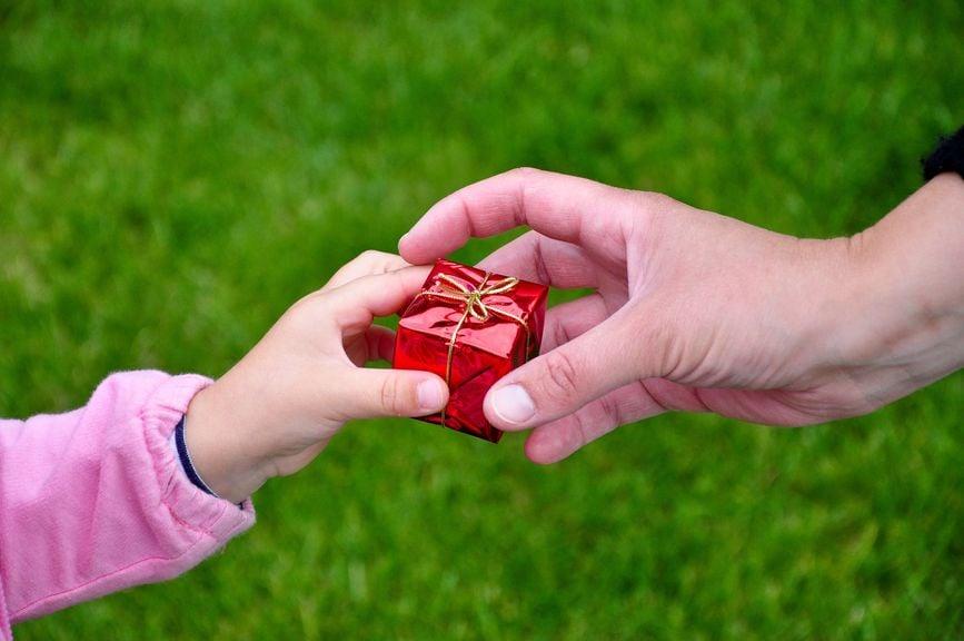 Kinderhand gibt ein kleines Geschenk an eine Frauenhand