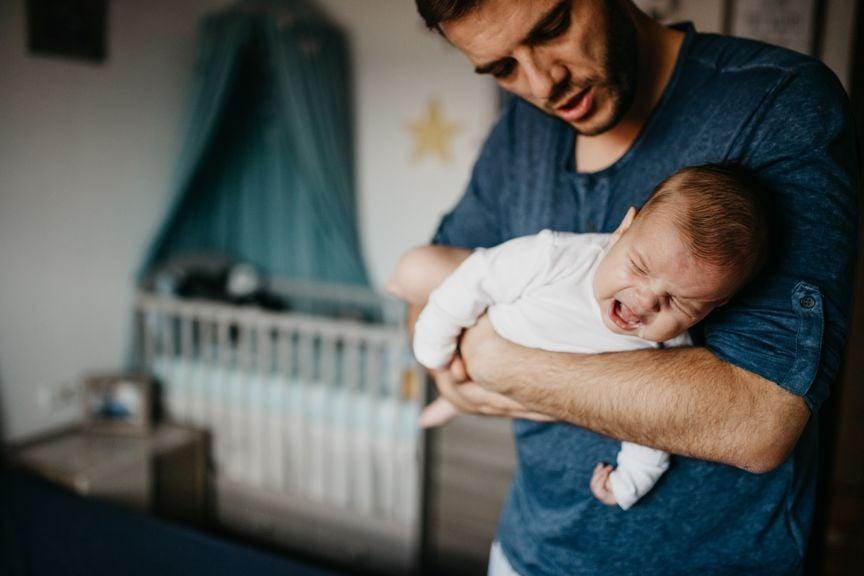 Vater trägt weinende Baby im Fliegergriff