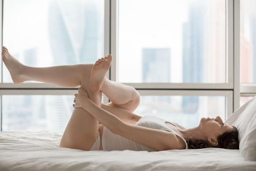 Frau macht Übungen im Bett