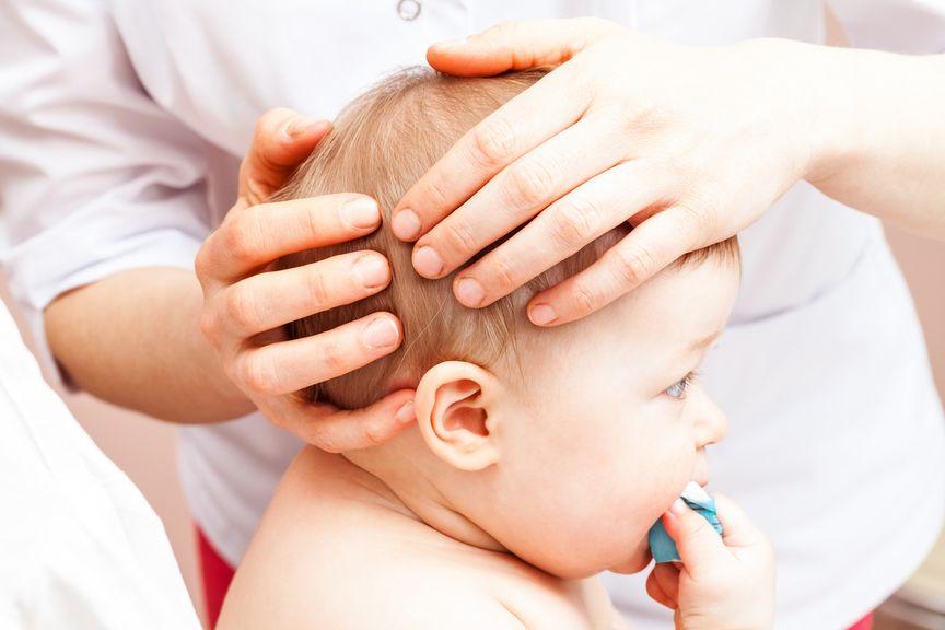 Hände am Kopf des Babys