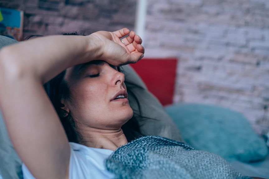 Frau im Bett fasst sich an die Stirn