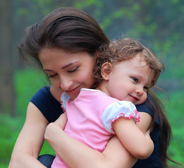 Mutter kniet vor Kind und nimmt es in den Arm
