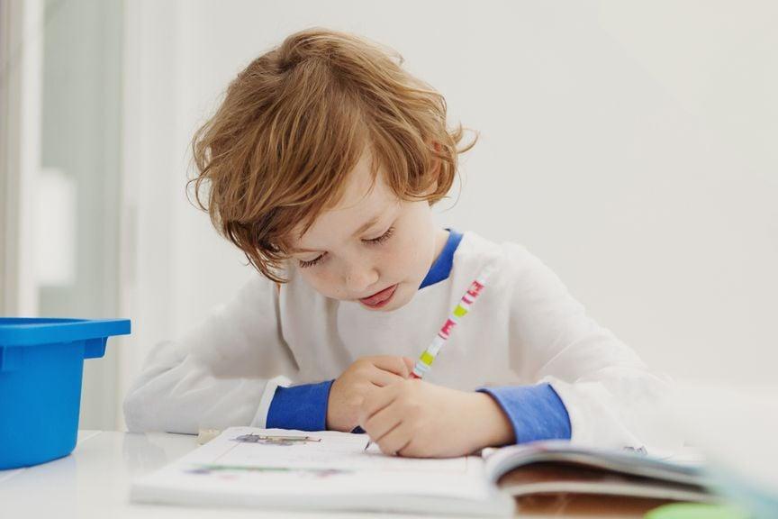 Schulkind schreibt mit Links