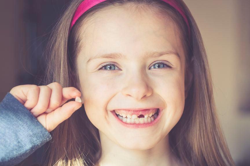 Mädchen mit Zahnlücke und Milchzahn