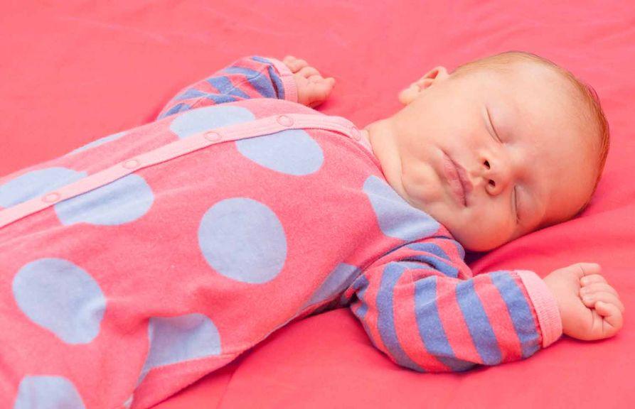 Baby im Schlafsack schläft auf dem Rücken