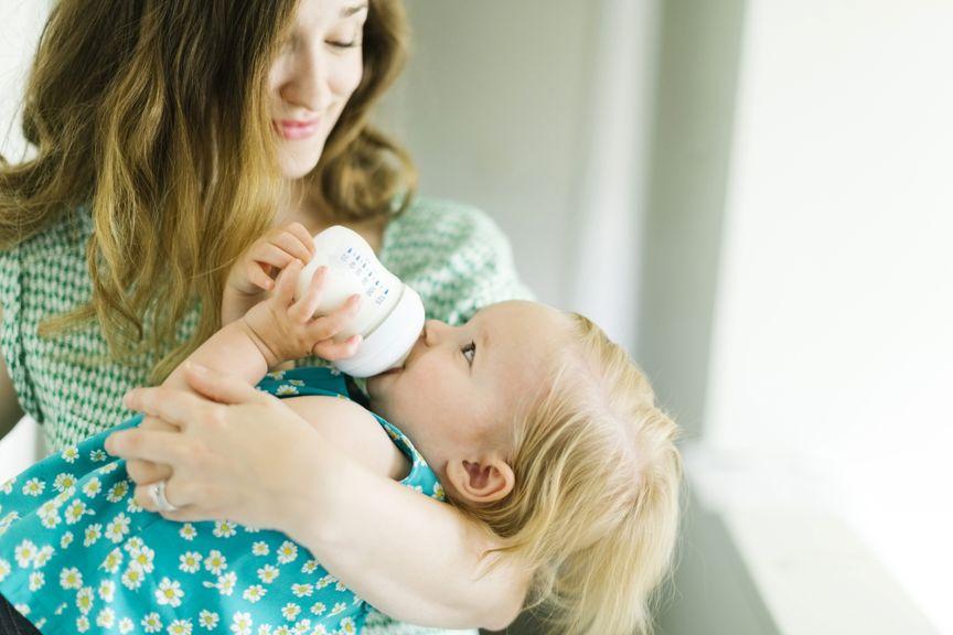 Mutter hält ihr Kind beim Schoppen trinken