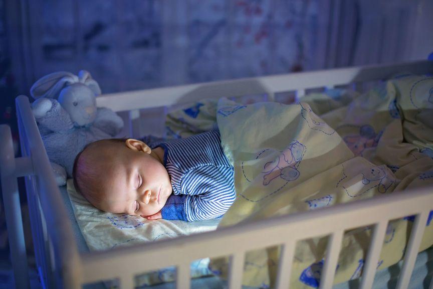 Baby schläft im Gitterbett