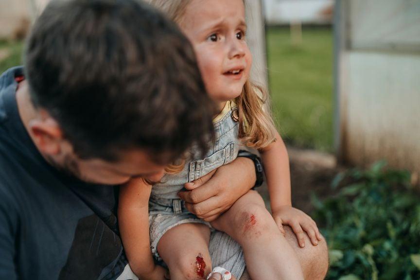 Vater versorgt blutende Wunde seiner Tochter