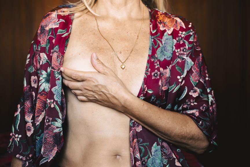Frau fasst sich an die rechte Brust