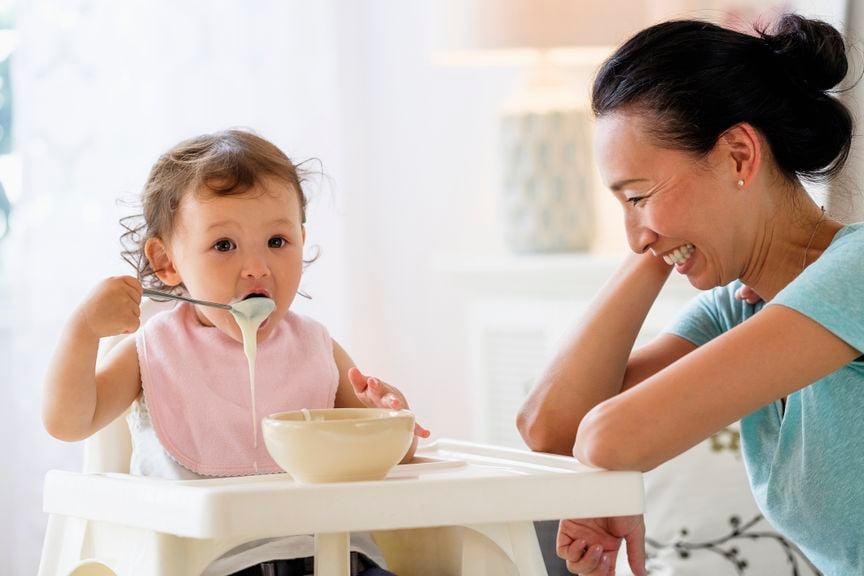 Kind kleckert mit Essen, Mutter lacht