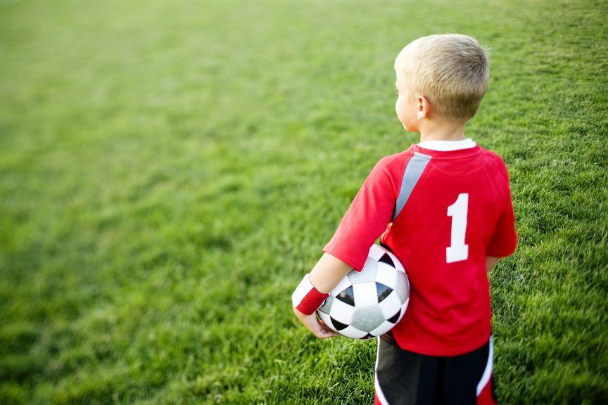 Junge im Fussballdress und Fussball