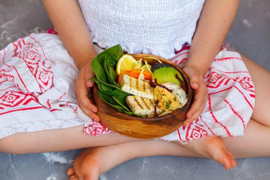 Mädchen mit einer Schale Tofu und Gemüse