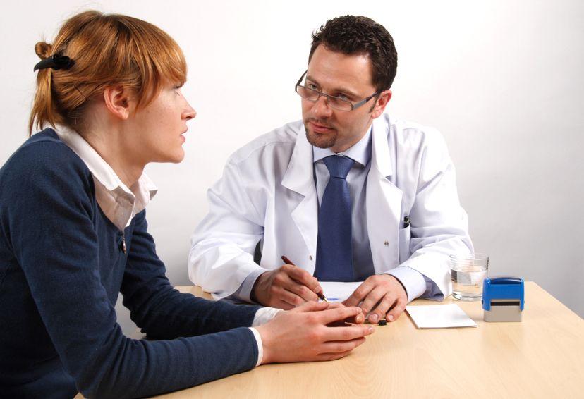 Frau sitzt mit dem Arzt am Tisch im Gespräch