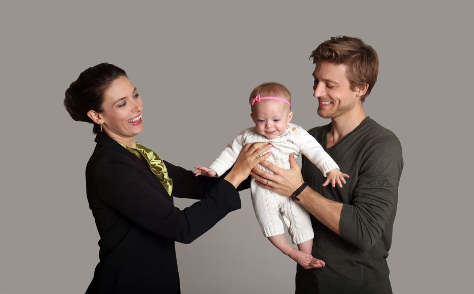 Mutter übergibt das Baby dem Vater