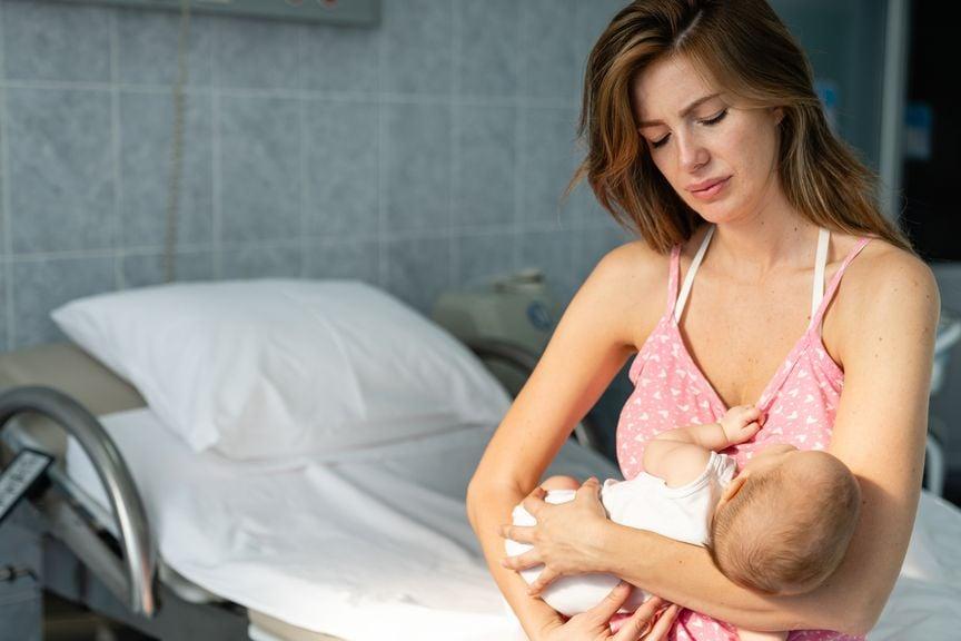Mutter im Spital hält ihr Neugeborenes
