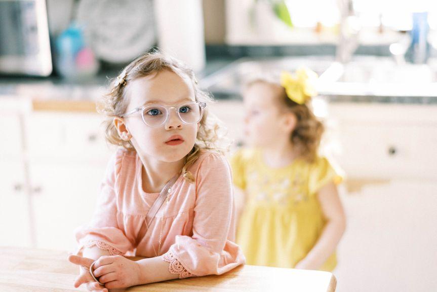Mädchen mit Brille sitzt am Tisch