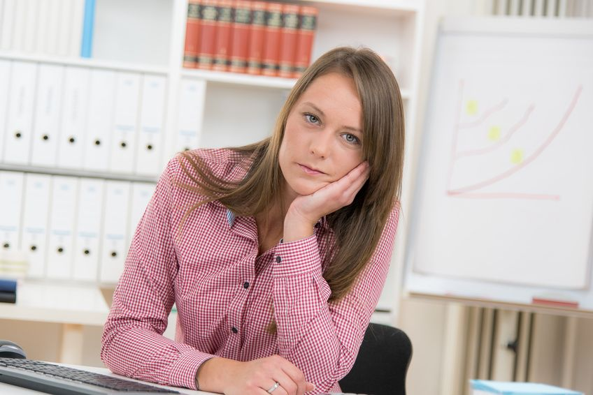 Frau stützt Kinn auf am Arbeitsplatz