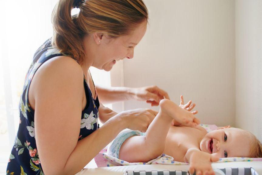Mutter und Baby haben Spass beim Windelwechseln