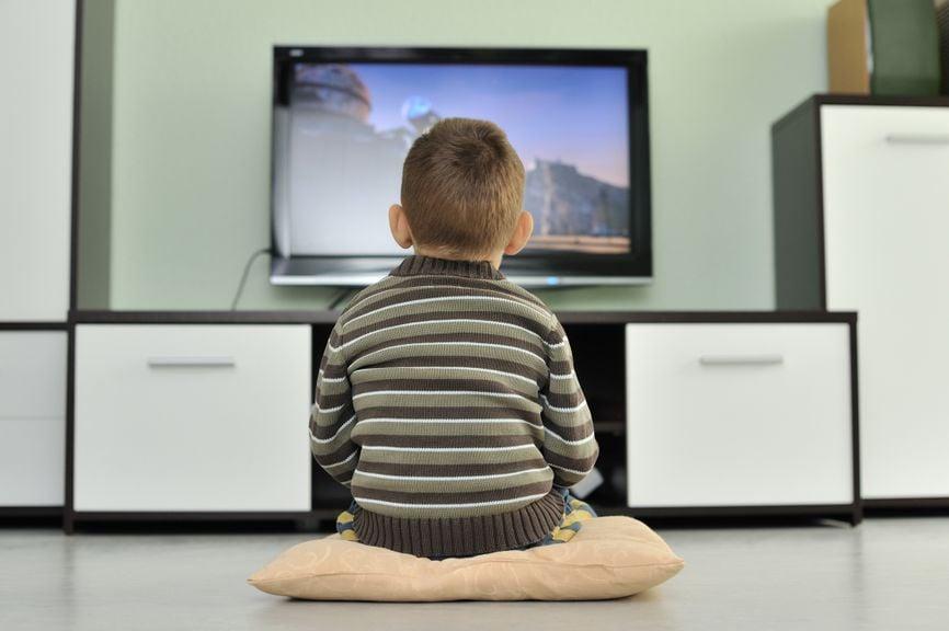 Kind sitzt alleine vor dem Fernseher