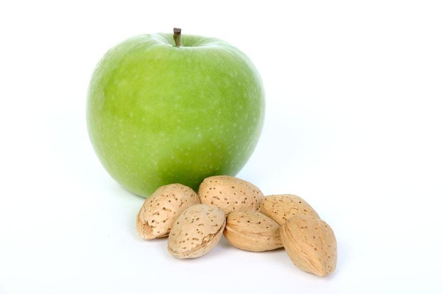 Grüner Apfel und Mandeln in der Schale