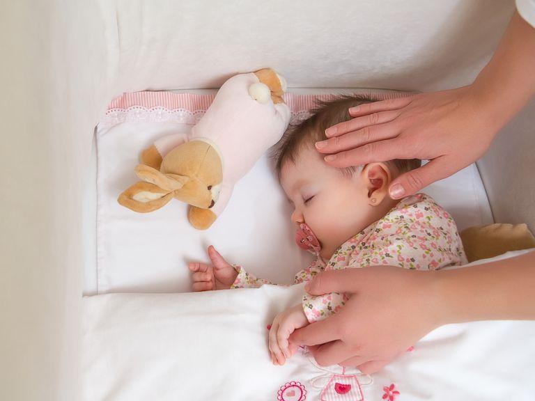 Mutter deckt das Baby zu, streichelt über den Kopf